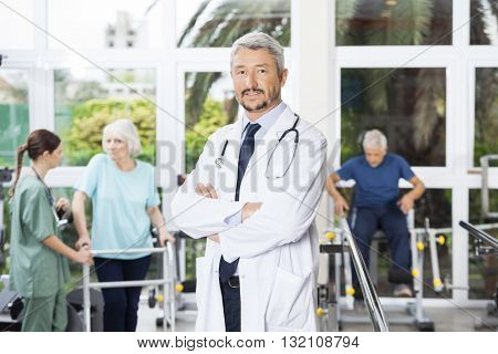 Confident Male Physiotherapist Standing Arms Crossed In Rehab Ce