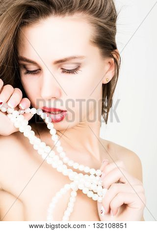 close-up portrait of a beautiful girl with red lips, holding a pearl necklace. mouth open, pearls touches her lips. Red Sexy Lips and Nails closeup.