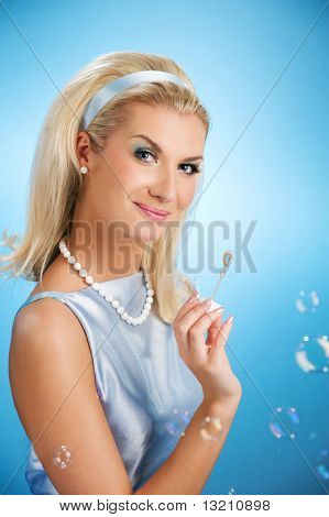 Beautiful young woman blowing soap bubbles