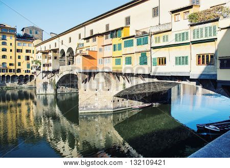 Beautiful Ponte Vecchio is mirroring in the river Arno Florence Tuscany Italy. Travel destination. Vibrant colors. Segmental arch bridge. Quiet water level. Cradle of the renaissance.
