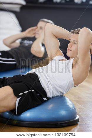 Man Performing Crunches With Friend In Gym