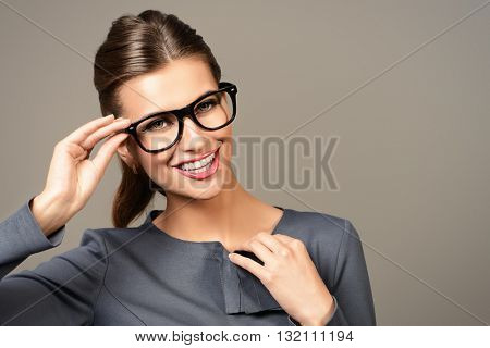 Optics style. Portrait of a beautiful smiling young woman wearing elegant glasses. Beauty, fashion. Cosmetics, make-up. Business style.