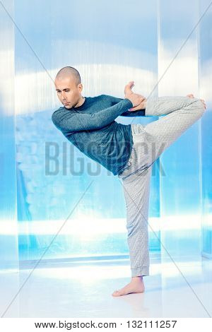 Yoga energy concept. Experienced yoga master performs different poses and exercises. Studio shot.