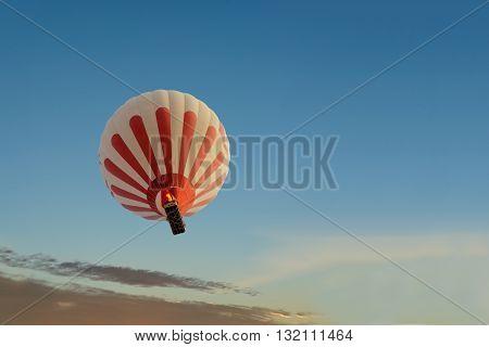 A hot air baloon rising high with dawn sunlight.