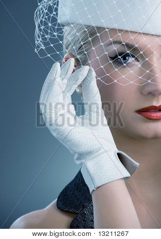 Hermosa joven en blanco sombrero con velo neto. Retrato de retro