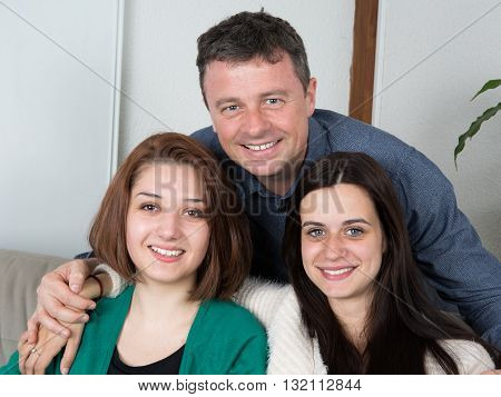 Portrait Of Father And Two Daugther Sitting Together On Couch.