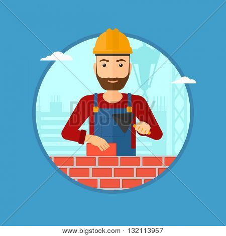 A hipster bricklayer in uniform and hard hat. Bricklayer working with a spatula and a brick in hands on construction site. Vector flat design illustration in the circle isolated on background.