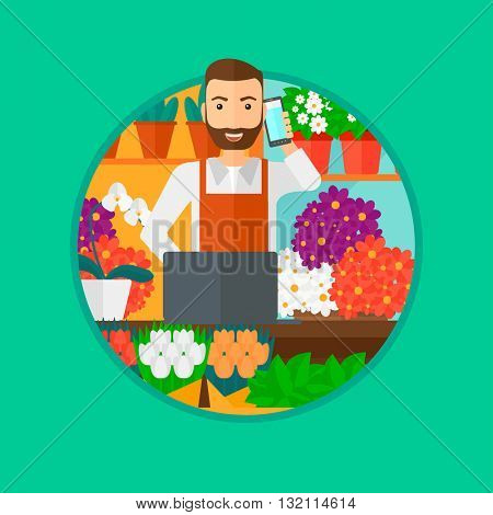 A hipster florist with the beard using telephone and laptop to take orders. A florist standing behind the counter at flower shop. Vector flat design illustration in the circle isolated on background.