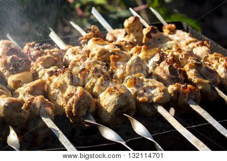 Skewers with a meat kebab on the grill with smoke outdoors