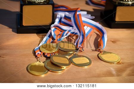 Gold medals with ribbons Russian flag on wooden background