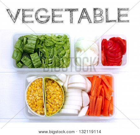 Vegetable slice in plastic box stand by for cook Tomatoes carrots onion gourd radish boiled corn plastic prepared ready slice All I keep it in Refrigerated are always fresh. Photo on white wood isolate.