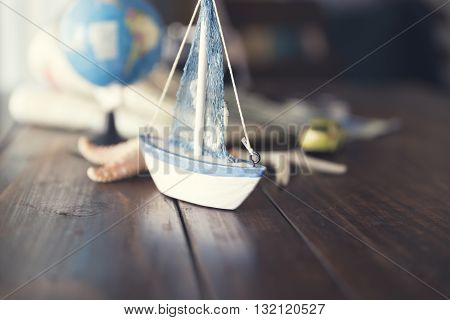 Globe, Ship And Car Figurine, Map, Starfish On Wooden Table For Use As Traveling Concept (vintage To