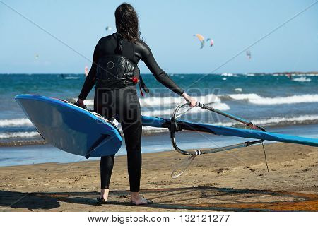 Girl with blue windsurfing on beach where the sun shining, kitesurfing in the background