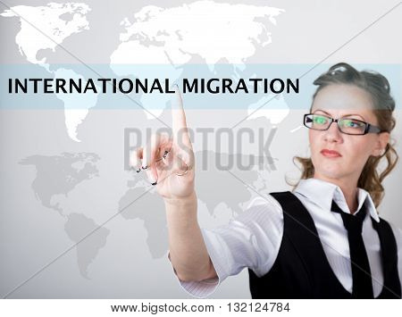 International migration written in search bar on virtual screen. technology, internet and networking concept. Internet technologies in business and home. woman in business suit and tie, presses a finger on a virtual screen.