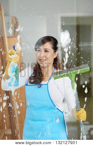 Asian mature housewife cleaning window with special spray
