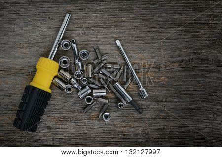 Screwdriver with allen and bits on wood surface