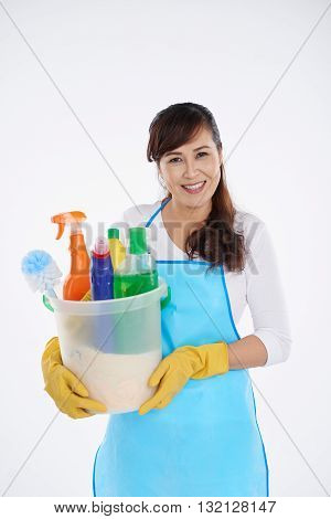 Smiling Asian housewife with basket of cleaning supplies