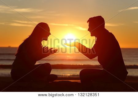 Portrait of a side view of couple or friends silhouette dating and falling in love with a boyfriend giving the sun to his girlfriend outdoors at sunset
