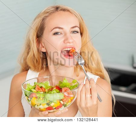 Young woman eating vegetable salad in the kitchen