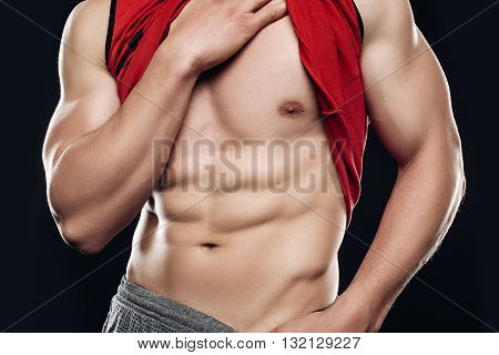 Close portrait of a naked torso. A man in a shirt undone, a denim outfit. Naked torso muscles cubes. Posing in the Studio. Brown background
