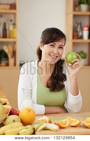 Female vegetarian with many fruits on table in front of her