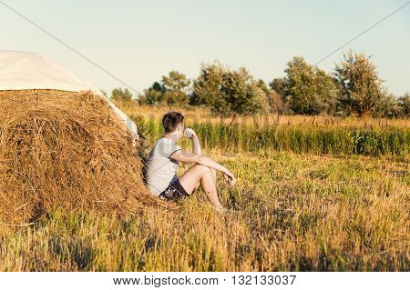 Young Man Tourist Resting Near Haystack
