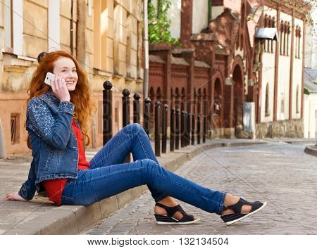 lonely girl tourist sits on the curb and talking on the phone and laughing