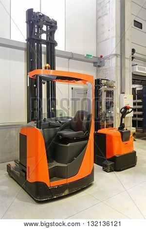 Forklift and Pallet Truck in Distribution Warehouse