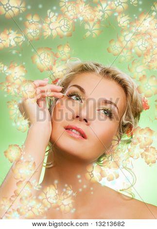 Hermosa joven con flores frescas en su pelo mirando hacia arriba. Concepto de la primavera.