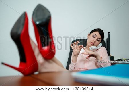 Relaxed businesswoman with legs on the desk