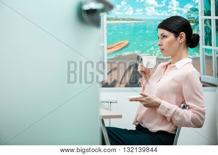 Woman resting with cup of in office kitchen.