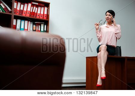 Businesswoman talking on the phone in office.