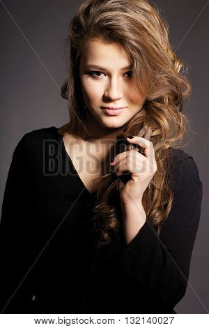 Young Beautiful Girl With Wavy Hair On A Black Background. Young Sexy Woman.
