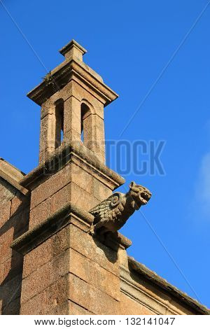 Gargoyle on the facade of breton church , Brittany , France