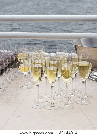 Sparkling champagne poured into glass transparent tall wine glasses at corporate parties on the cruise boat and the sea in the background