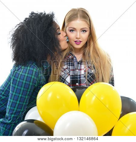 Two happy hipster girls having fun and kissing each other with balloons over white background