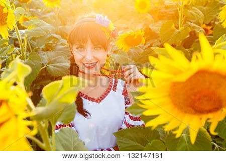 Beautiful young girl in traditional ukrainian blouse embrodery looking to camera on a sunflower plant at sunset backlight.