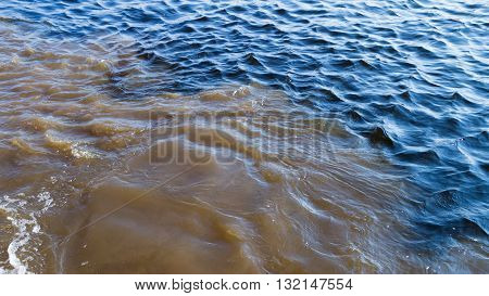 brown gray dirty muddy water mixed with pure blue sea water and the environment is polluted