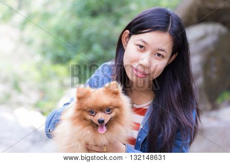 Thai woman and pomeranian with rock in river