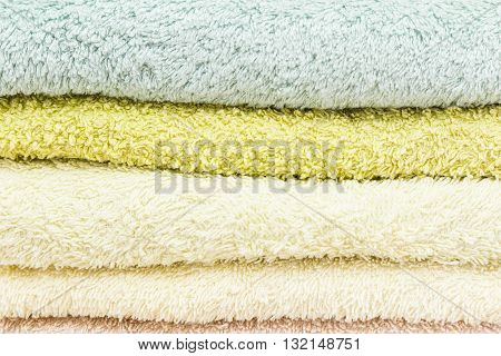 freshly laundered bath towels stacked and folded in different colors