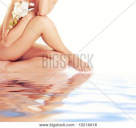 Weibliche Beine mit weiße Orchidee