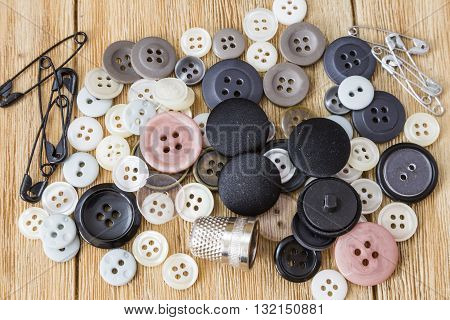 Various sewing buttons and safety pins on a wooden table
