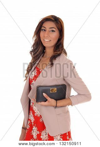 Young lovely woman in a red dress and jacket holding her handbag standing isolated for white background.