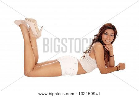 A tall gorgeous woman lying on the floor in beige shorts looking into the camera isolated for white background.