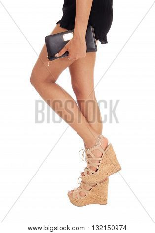 A closeup image of the long legs of a young woman standing in high heels holding a small handbag isolated for white background.