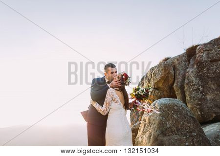 Romantic newlywed husband kissing hin new wife in sunset lights on majestic rocky mountain cliff.