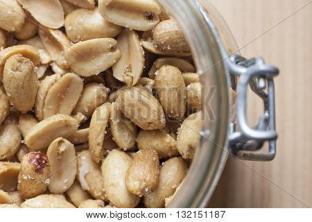 Open canning jar with fried salty peanuts. Selective focus. High angle view