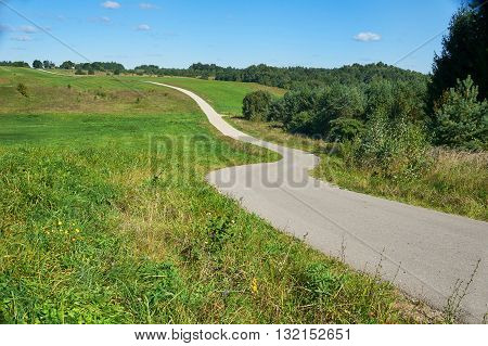 Narrow winding road in sunny summer day.