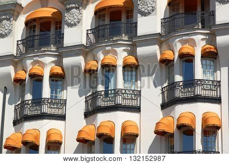 Part of wall of building with colorful awnings in sunny day