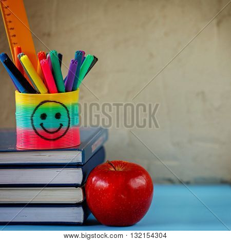 Group of school supplies and books and red apple over on background.School stationary equipment